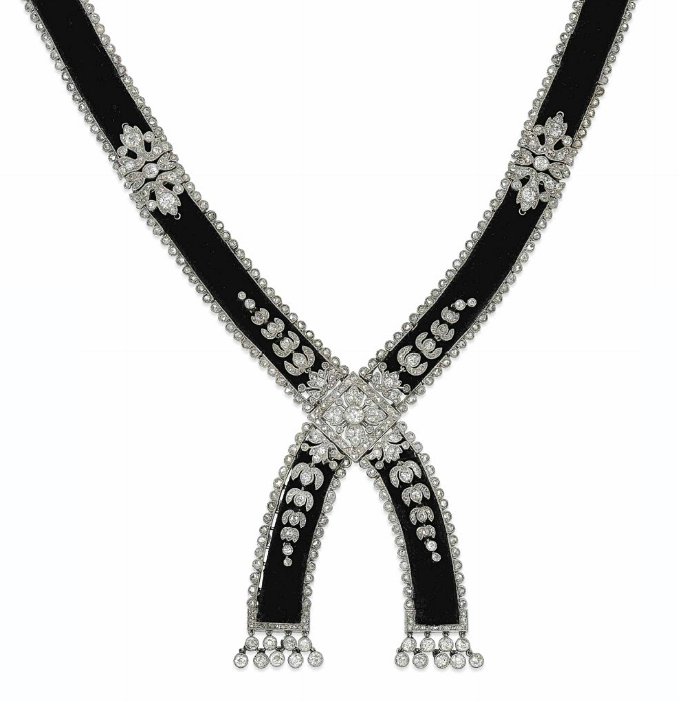 A BELLE EPOQUE VELVET AND DIAMOND NECKLACE, BY CARTIER  Of cross-over tassle design, millegrain-set throughout, the black velvet collar with diamond-set scalloped border and stylised acanthus leaf highlights, to the similarly-set quatrefoil centre and radiating foliate panels, with diamond collet tassel terminals, circa 1905, French marks for gold, 50.0cm long, velvet is a later replacement Signed Cartier, Paris and no.2987