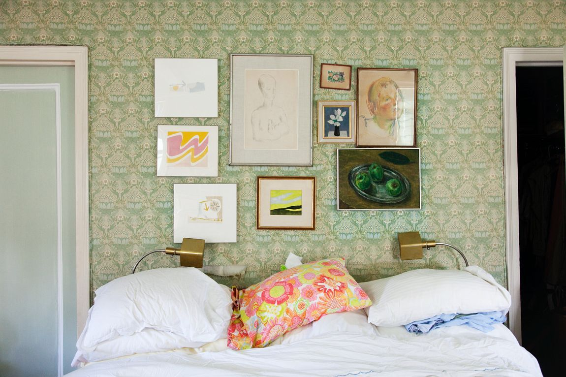 Is it the wallpaper? The pillow? The crooked pictures? Seems like the good life, that's all. Wouldn't mind the kids crawling in bed here.