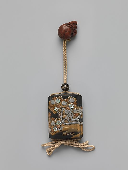 Case (Inrô) with Design of Maple Tree and Stream In the style of Ogata Kôrin (Japanese, 1658–1716) Period: Edo period (1615–1868) Date: 18th–19th century Culture: Japan Medium: Gold lacquer with dark gray ishime, gold, red, black, and silver makie, pewter, and mother-of-pearl; Ojime: bead with autumn wild flowers; Netsuke: rat eating peach; boxwood