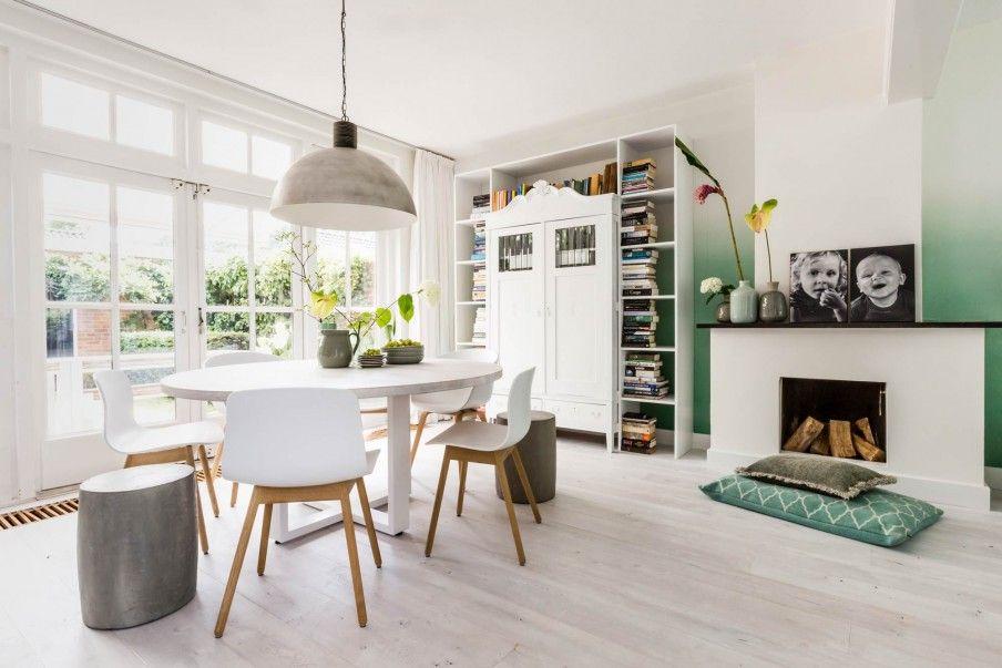 Ronde witte eettafel met boekenkast en groen behang bij deborah