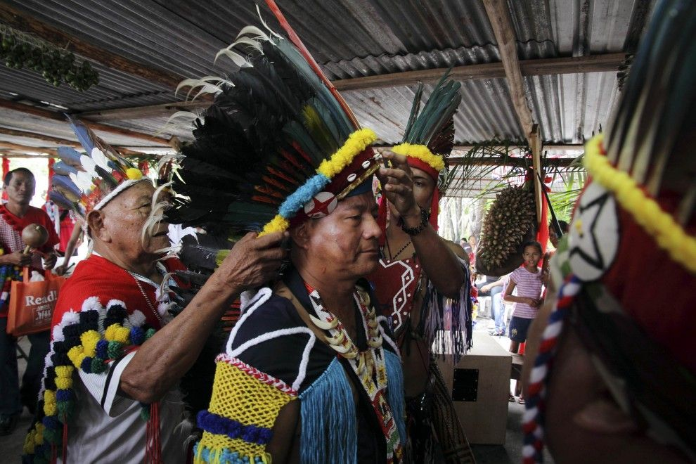 Surinamese Arawak, Theo Jubitana (C), has a headdress put on him during the ceremony of his inauguration as the new captain, the head of his village, at Hollandse Kamp village in Para February 4, 2012. After 21 years, the Awaraks of Hollandse Kamp elected a new board, with Jubitana as the leader, that calls upon villagers to continue the fight for the ownership of their land.