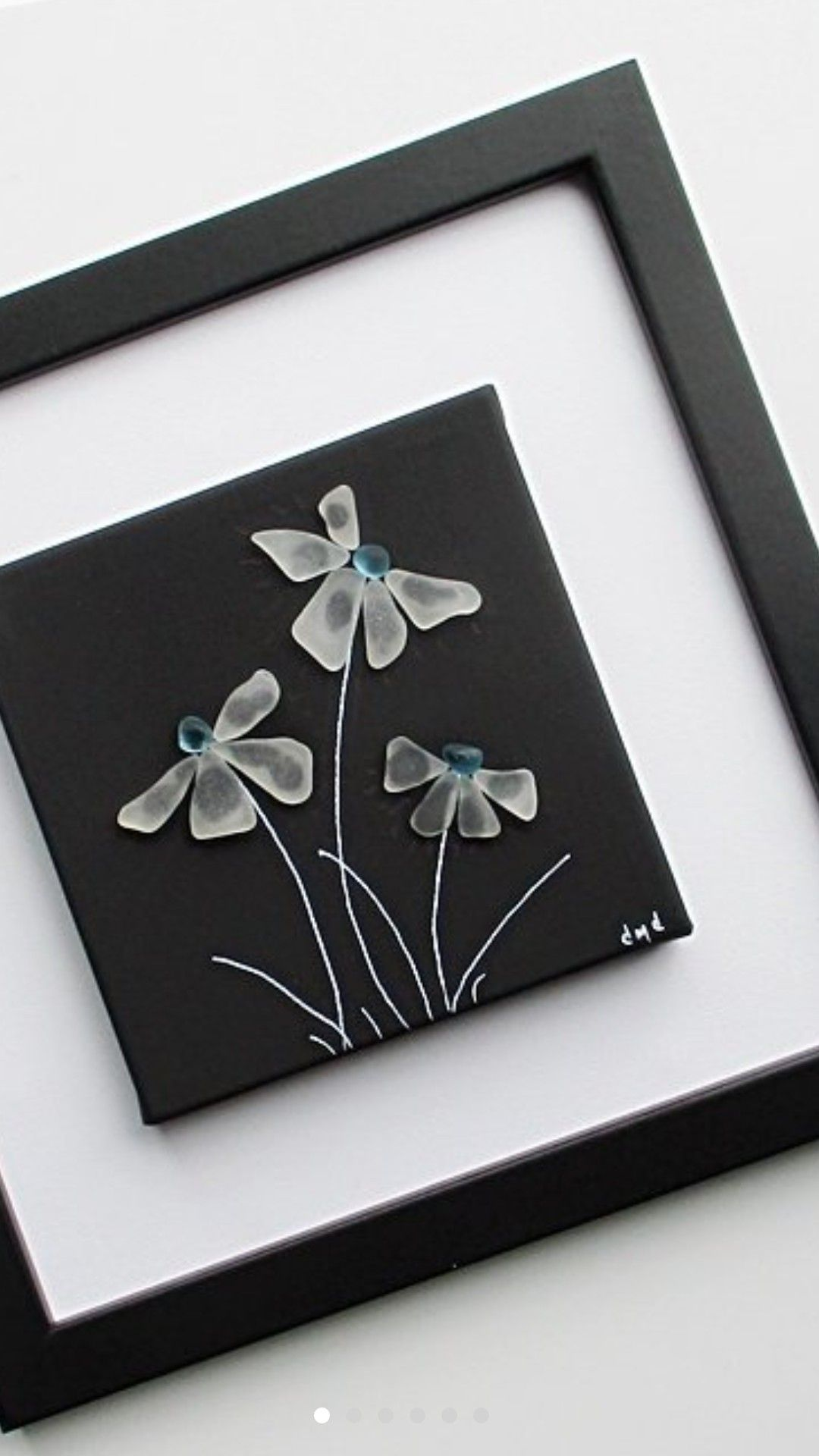 Photo of White sea glass flowers on black background.