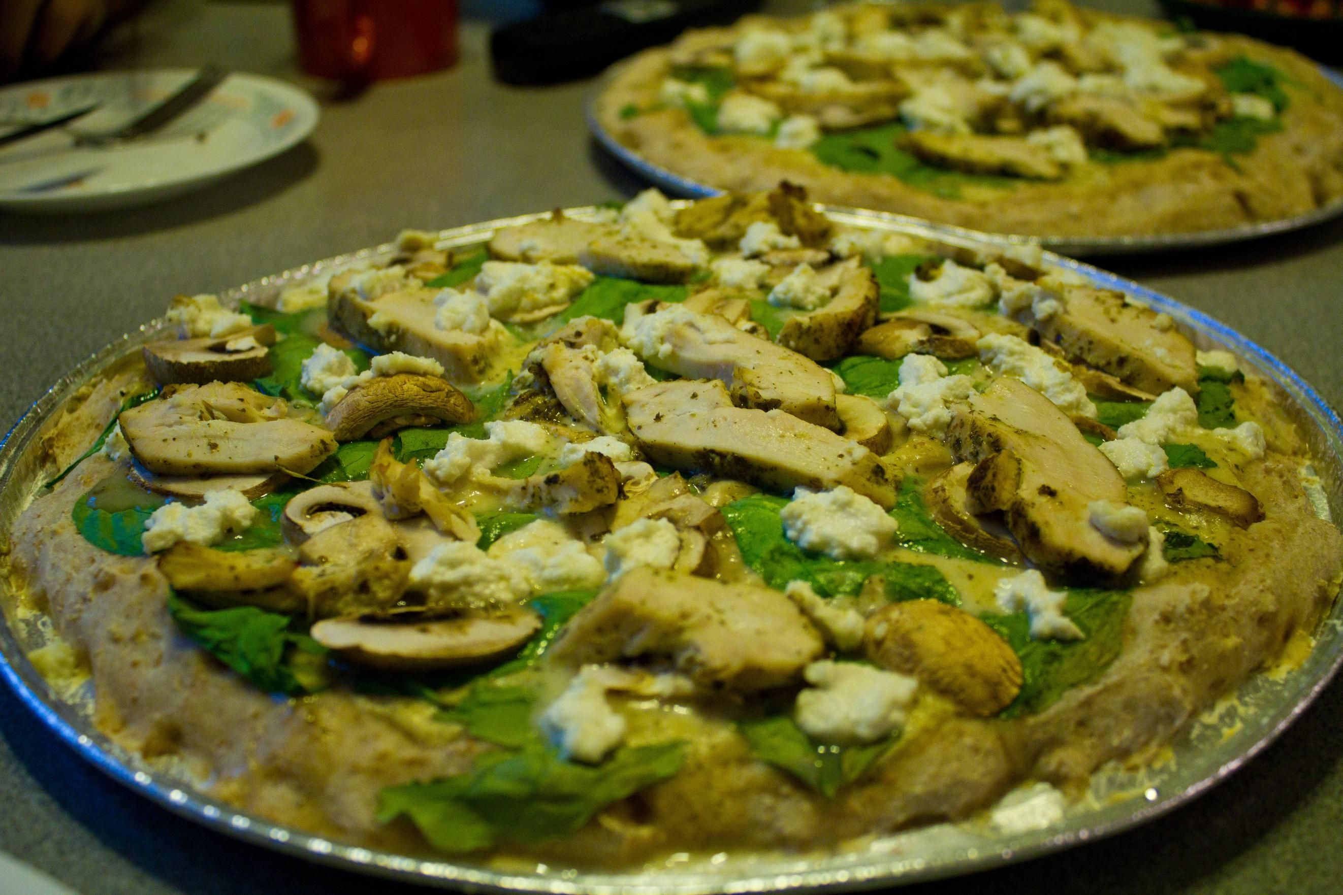 First attempt at pizza from scratch  alfedo sauce, spinach, pesto chicken, and mushrooms.