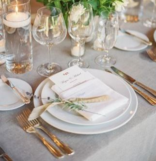 Menu tucking into folded napkin with a sprig of olive branch with ...