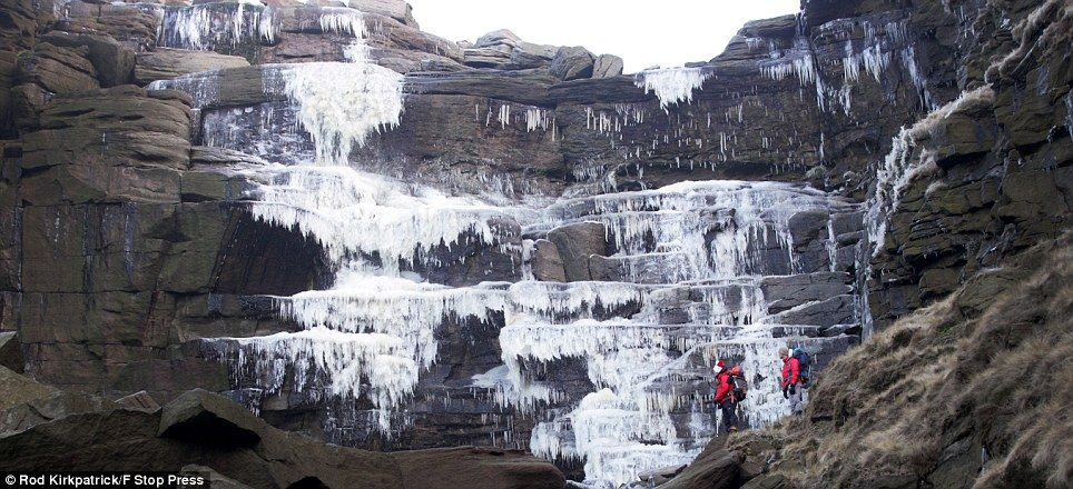 Water not-quite-fall: Climbers Simon Stokes and Mark Davies admire giant icicles along the frozen Kinder Downfall waterfall high in the Derbyshire Peak District  8/2/2015