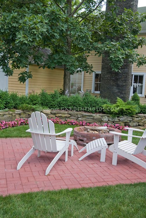 Brick patio in lawn grass with adirondack white wooden for Fireplace on raised deck