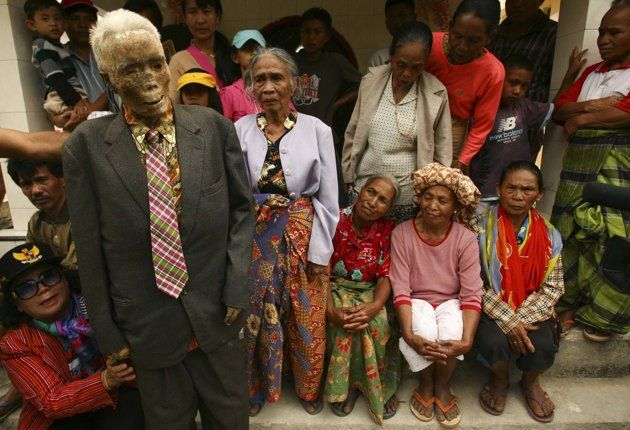 Family members hold up a mummy before giving it new clothes in a ritual in the Toraja district of Indonesia's South Sulawesi Province