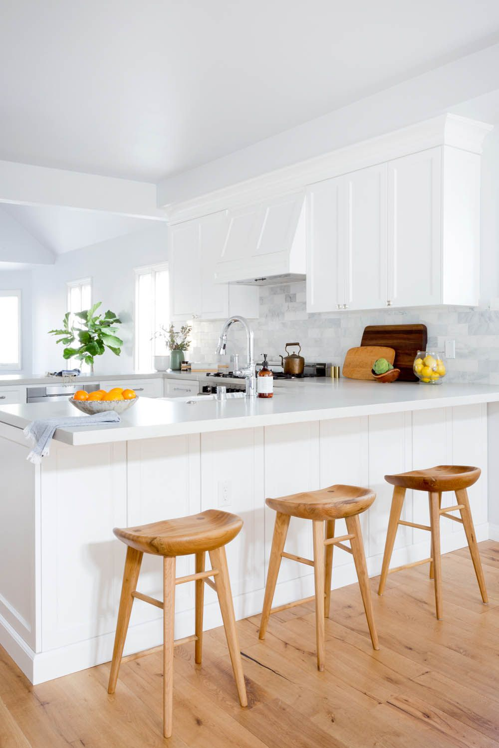Classic all white kitchen with wood stools // A Cape Cod in ...