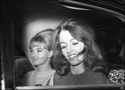 """Christine Keeler (foreground) & her friend, Mandy Rice-Davies (in back) two very young girls performing in seedy nightclubs and running with a fast rich and well connected crowd in 1962 London managed to bed several British Lords, Russian spies, and Members of PM's Government.  The scandal that ensued eventually brought down the conservative government and ended the promising political career of Cabinet Minister John Profumo.  Thus giving the scandal its name """"The Profumo Affair""""."""