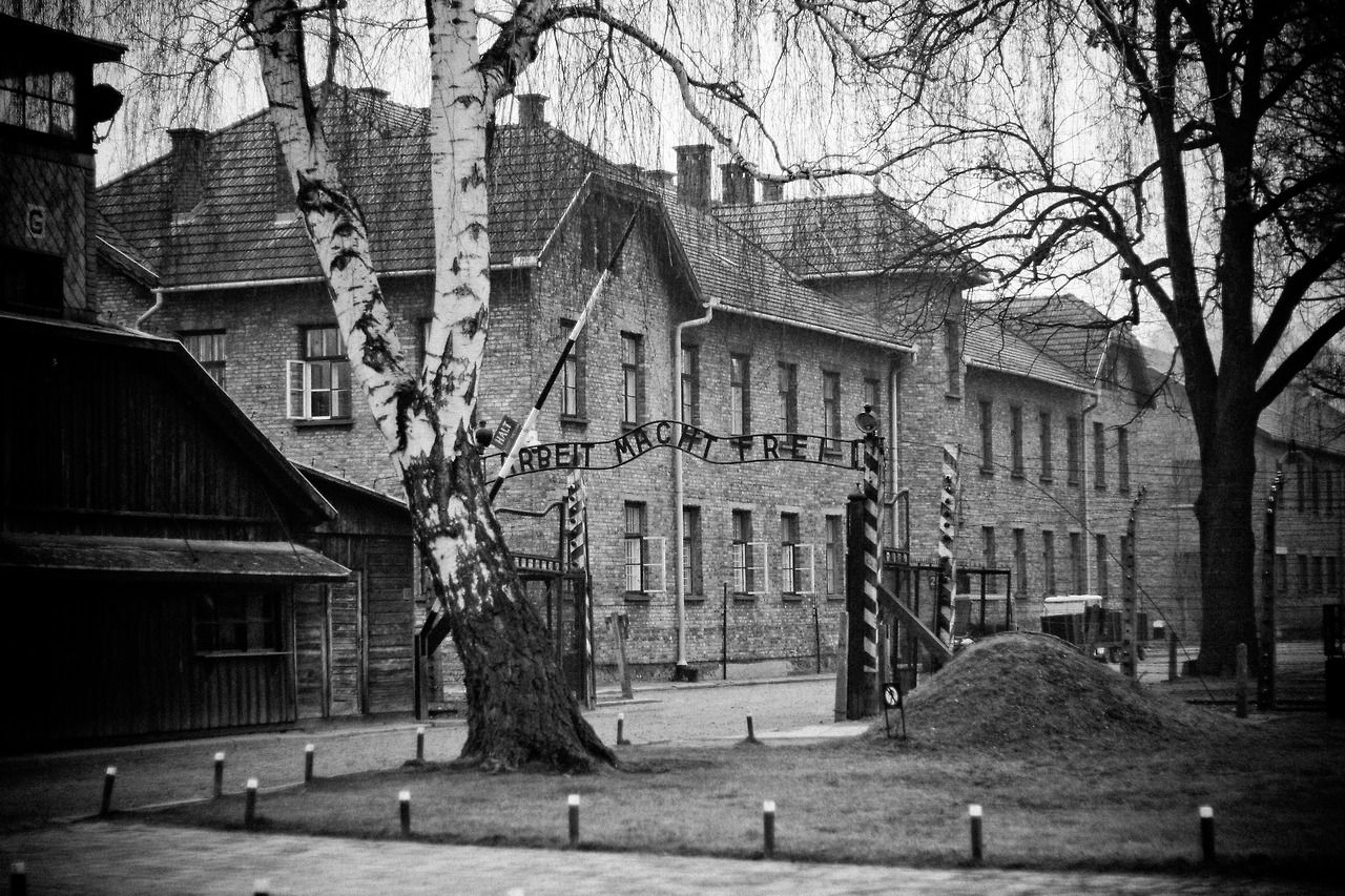 Main entrance to the Auschwitz I camp with the 'Arbeit macht frei' sign above the gate. Block 24 visible inside the fenced area.