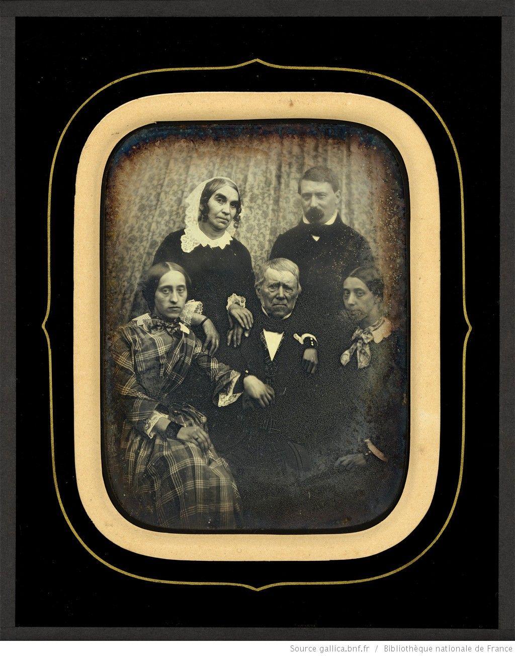 [Portrait de groupe : trois femmes et deux hommes posant devant un rideau] : [photographie] / Non identifié