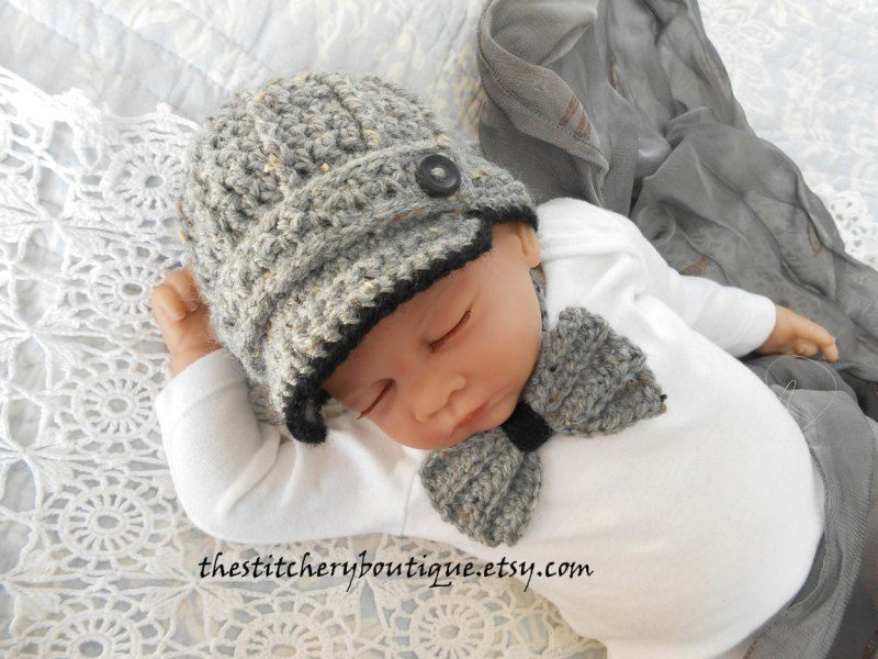 6ba46760942 Even newborn baby boys look dazzling in this crocheted light gray newsboy  hat with black lining embellished with a cute little black button.