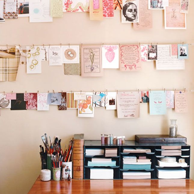 Pictures hanging from clothespins over a simple desk so cute workspaces inspiration