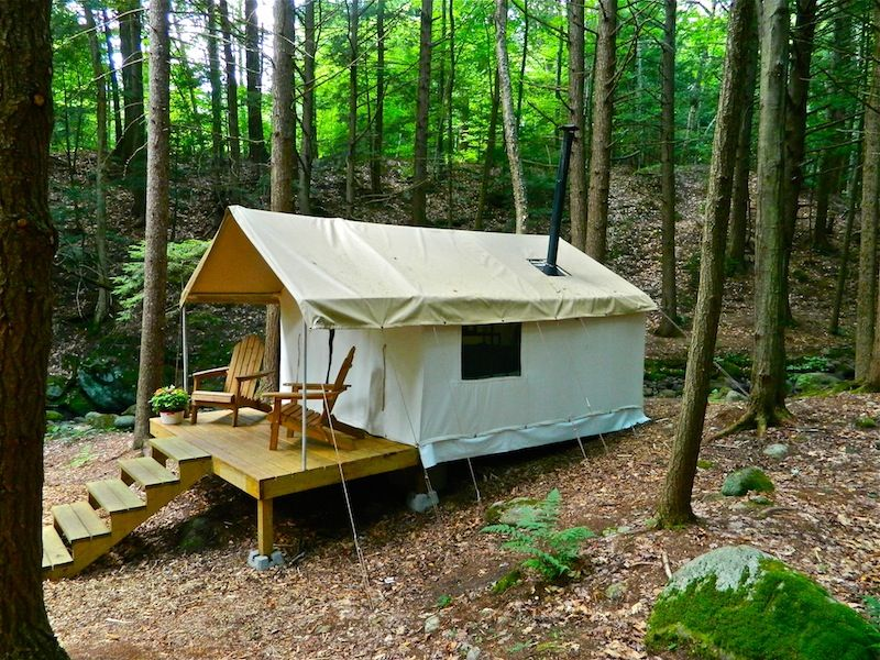 Canvas tent kept in shape by wooden exoskeleton, covered with translucent vinyl.