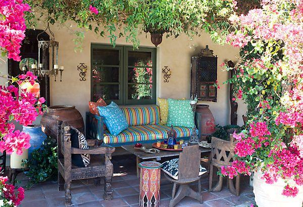 Preciosa terraza con mobiliario étnico y ambientación floral exuberante