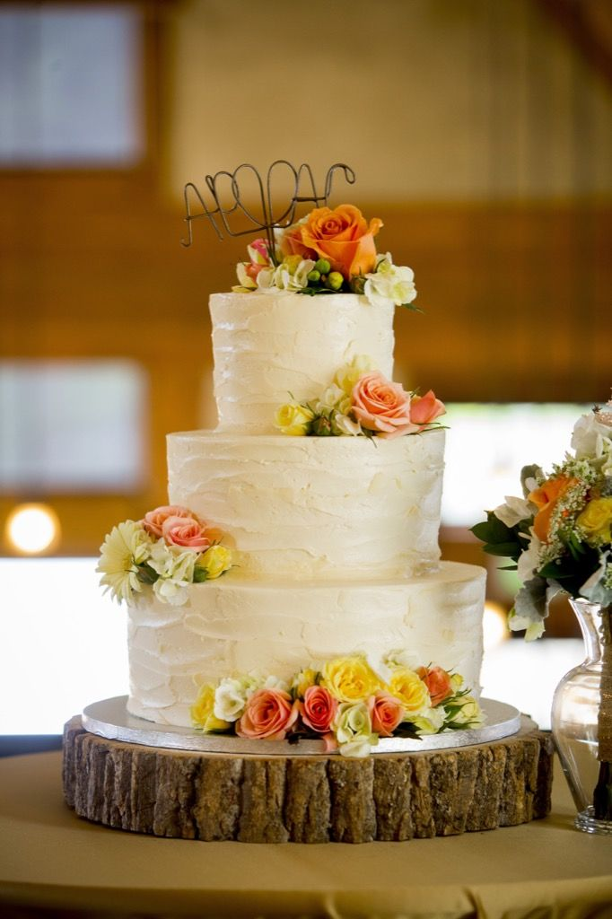 White cake with coral and yellow flowers. Three tier. Photographer ...