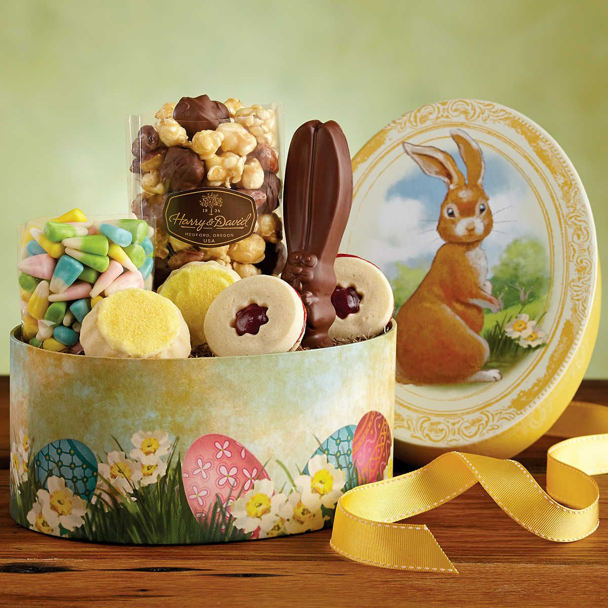 A gift box shaped like an egg and decorated for the holiday makes delightful easter gift basket idea with lovely oval basket motives idea and completed with yummy easter cakes and chocolates and cookies and candies negle Images