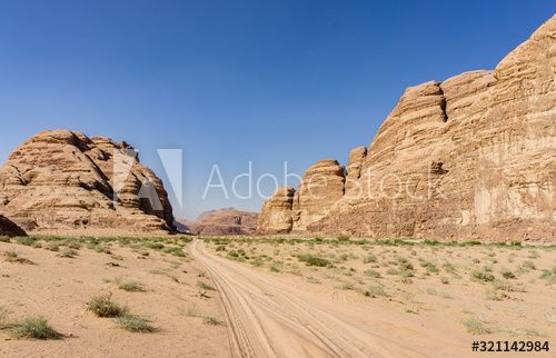 Magic mountain landscapes of Wadi Rum Desert, Jordan. Mountains in lifeless desert resemble Martian craters. Red sand and red rocks. There is place for text. - Buy this stock photo and explore similar images at Adobe Stock