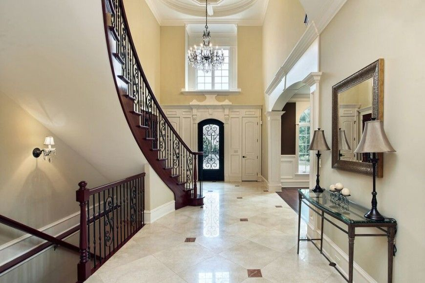 Another grand foyer seen from the rear of the space, looking towards the front door. A curved staircase leading upstairs disguises the lower staircase leading to the basement.