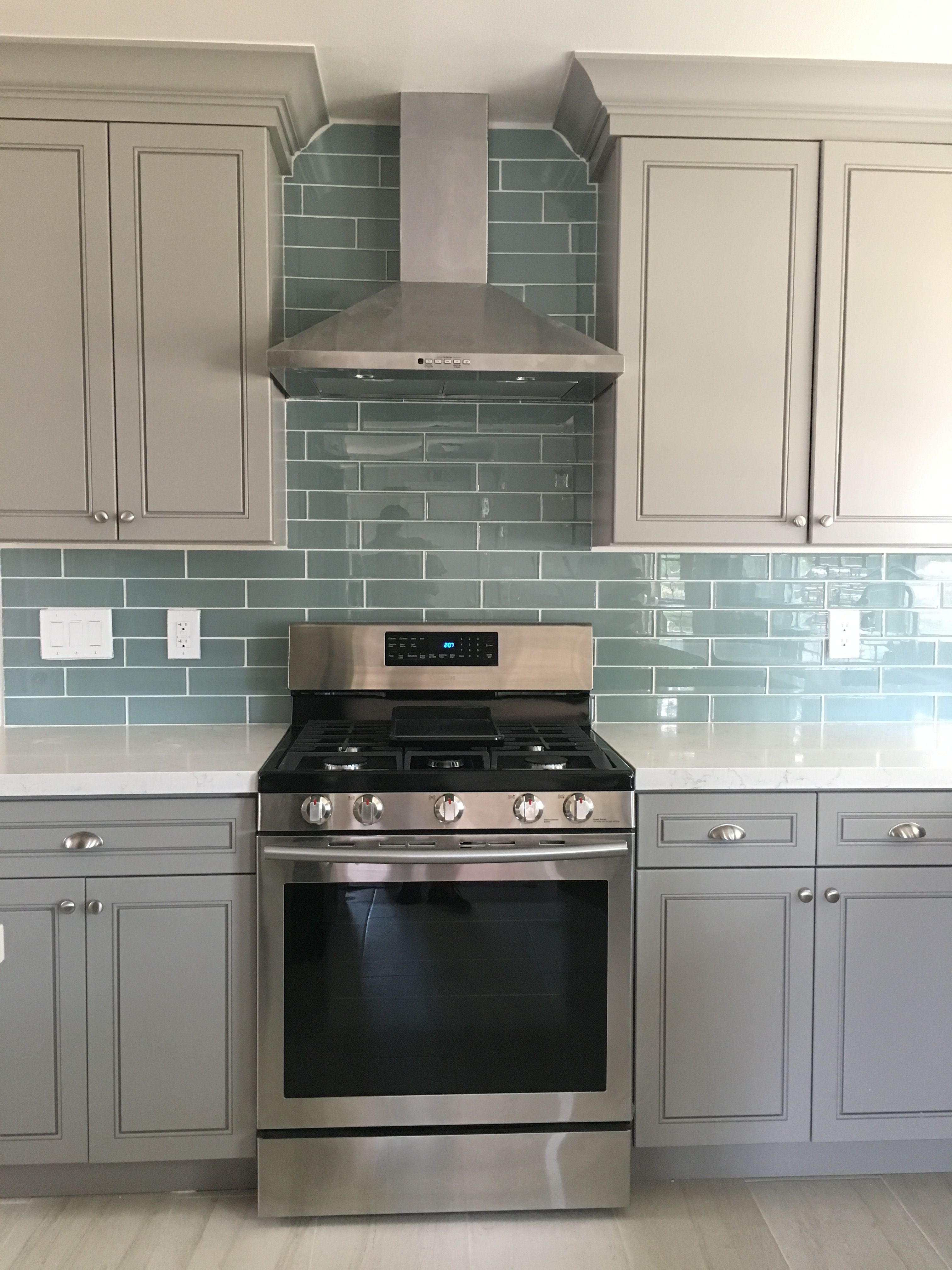 Blue Glass Tile Backsplash With Gray Cabinets And White Quartz