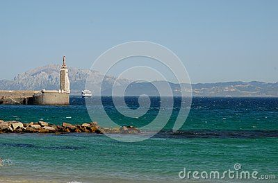 Photo made at the port of Tarifa Andalusia (Spain). In the image you see to the right of the lighthouse, get one of the ferries that shuttles between Spain and Morocco in which we see the mountainous coastline over the stretch of ocean that separates the two countries.
