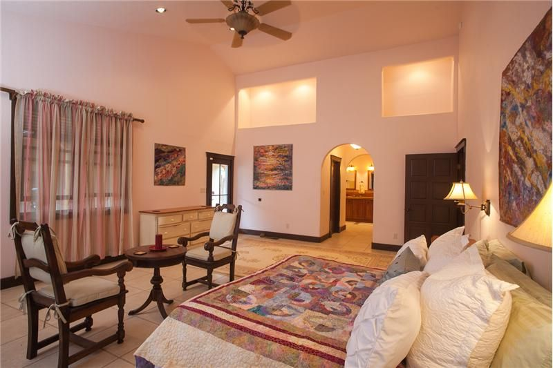 Master Bedroom in Leaping deer ranch. one of 7 bedrooms. Decorated with local inspiration. Sante Fe aesthetic! Local art on every wall. #tapestry, #wallhangings #fiberart by Marianne Williamson. Ranch for sale!