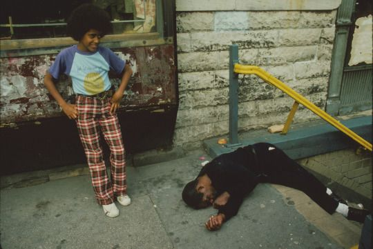 Boy looks over a man passed out in front of a subway entrance, Lower East Side, 1980.