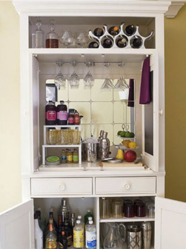 repurpose your old tv cabinet as a hideaway bar here she installed inexpensive hanging glass racks and used threetiered stacking shelves and trays to