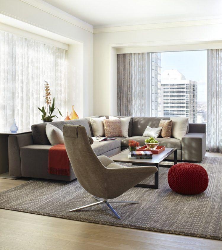 Déco salon moderne avec des coussins en blanc et marron sur la canapé gris pouf