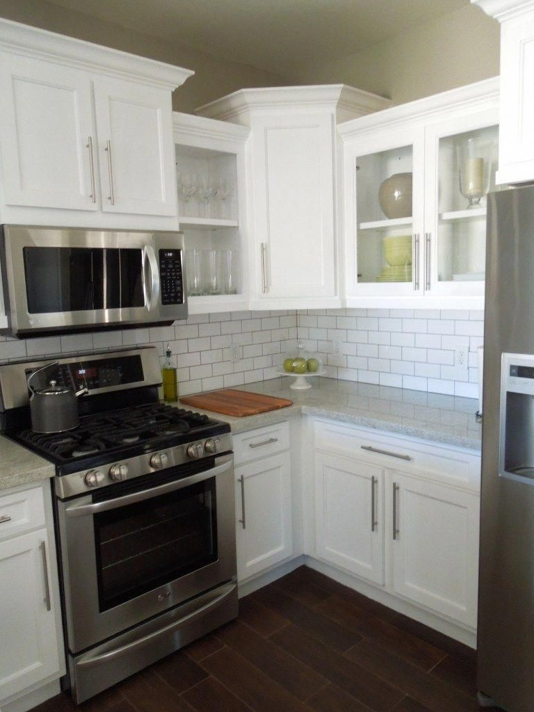 White Cabinets Staggered Height Cabinets Glass Front Cabinets Stainless Appliances Subway Kitchen Remodel Small Upper Kitchen Cabinets Kitchen Remodel Cost