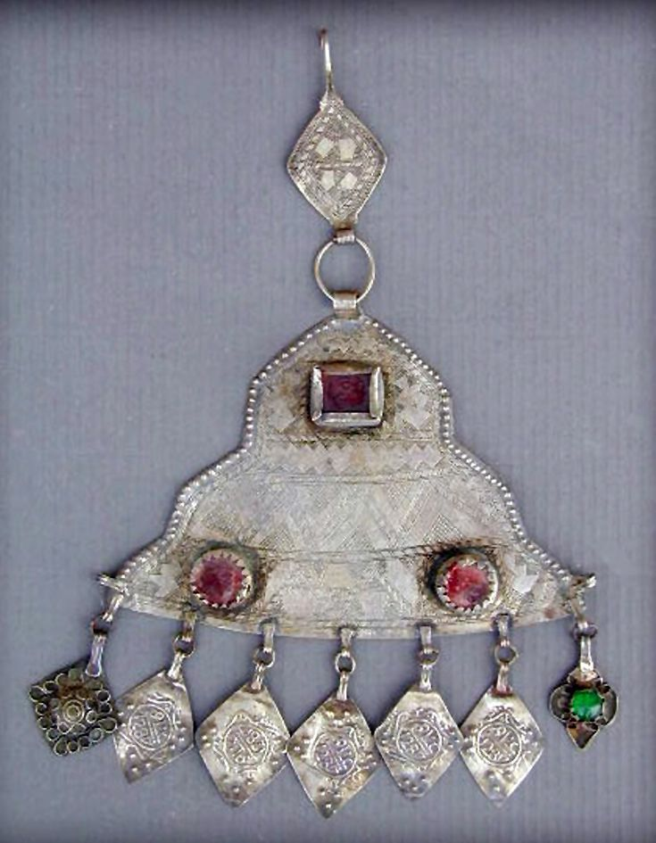 Morocco - Silver Berber head ornament from the Oasis of Foum Zguid, in the south. Low grade silver, with simple chased decor. | Early to mid 20th century. The dangles present the date of 1280 from Hegira.