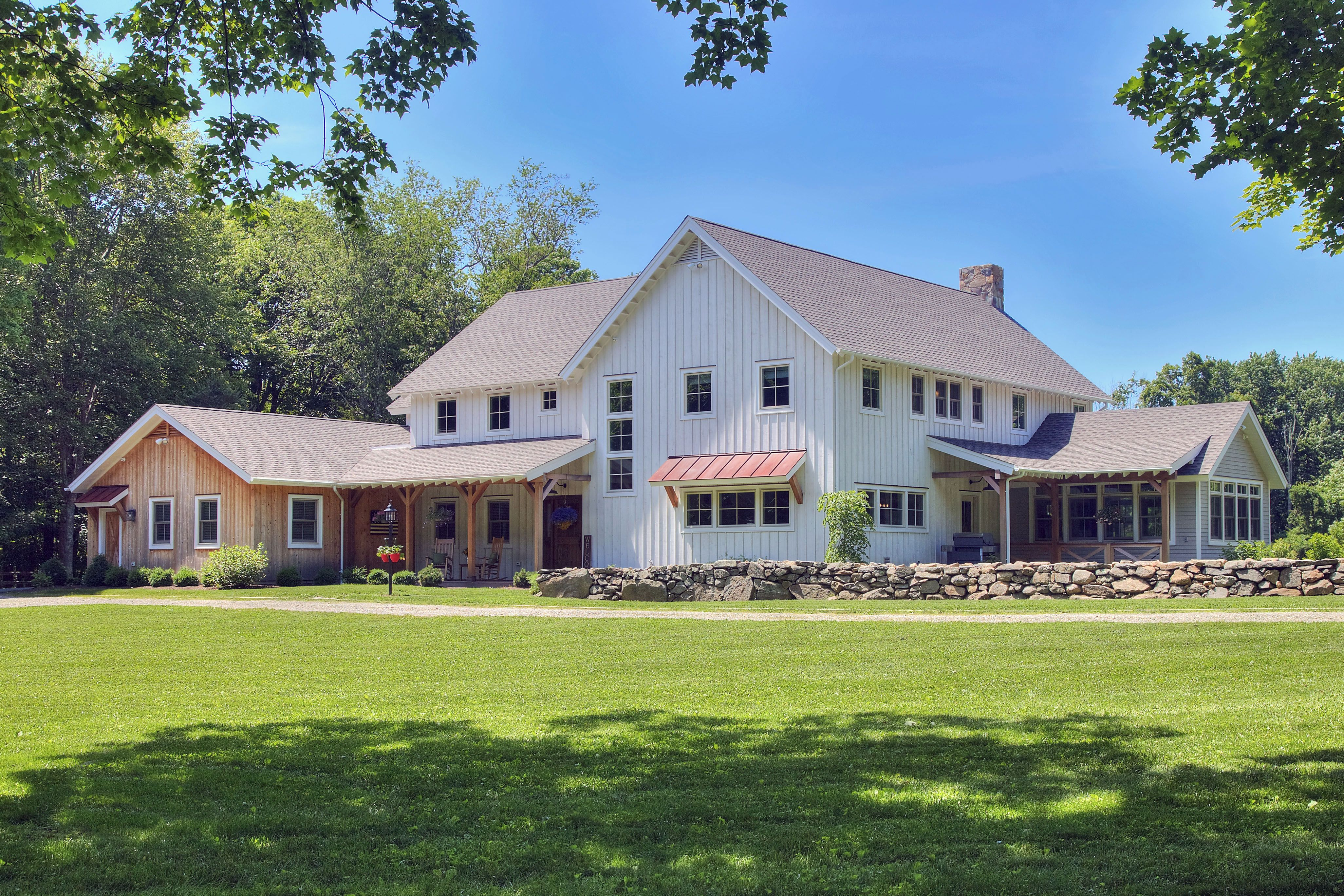 Traditional Farmhouse Featuring Board And Batton Siding Rusted Metal Roof And Vertical Cedar Siding Custom Home Builders Farmhouse Architecture Home Builders