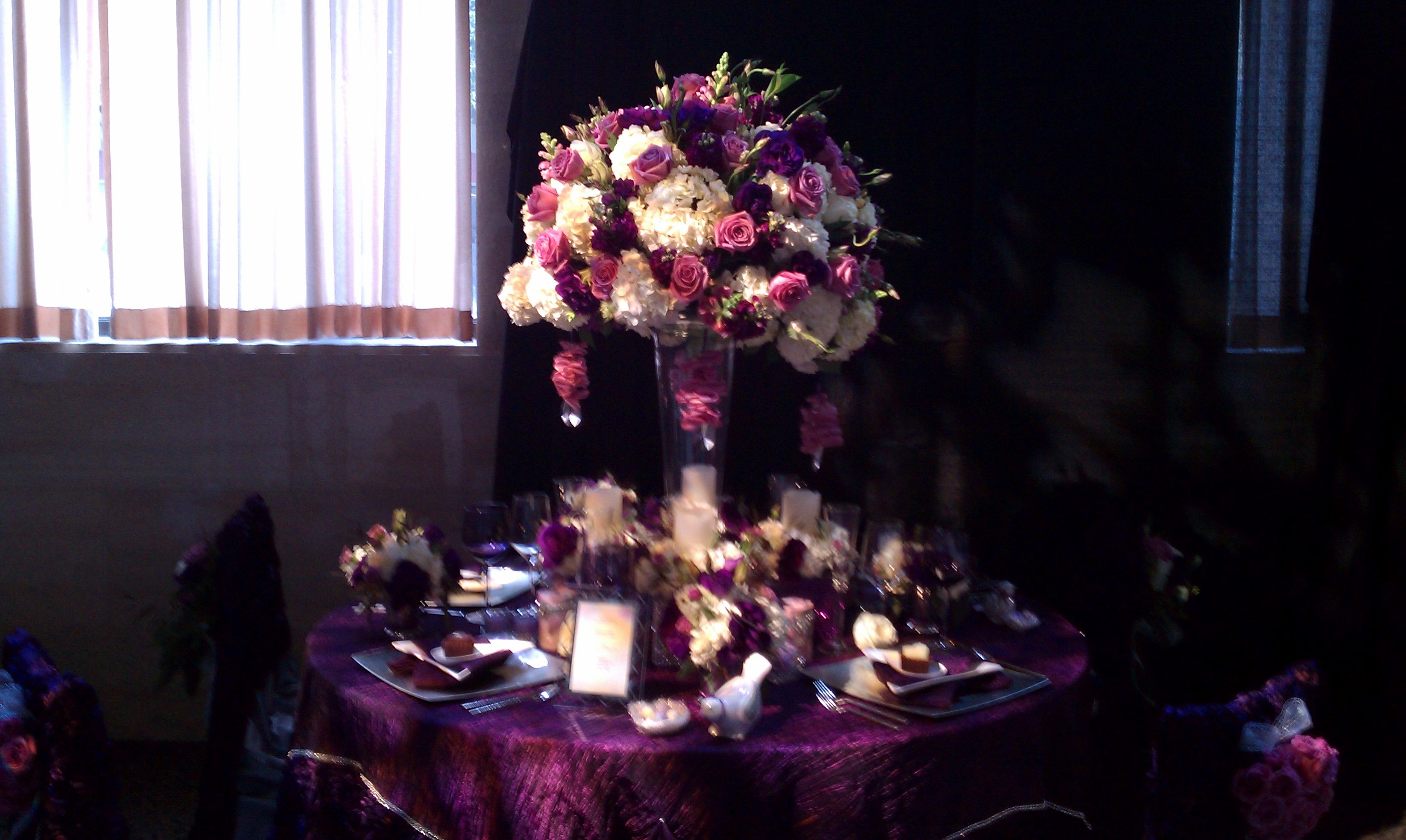 Wedding flower centerpiece in shades of purple and white. Look closely for all the layers of details...this is what will enchant and entertain your guests while sitting at a table like this...there are many layers and surprises for guests to discover, taking their breath away with wonder and fascination.  I used white hydrangea, lavender roses, purple lisianthus, purple stock and lavender snap draggons.