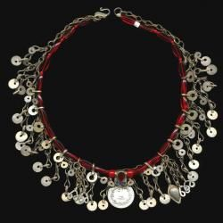 $38.00  Detailed two-layer necklace with red glass beads, chain fringe and Kuchi charm. The top later features lozenge shaped and round glass beads with small Kuchi dangles and a Kuchi coin charm with red and blue jewels. The longer layer is two-inch chain fringe and is just a bit longer than the top layer to peek out beneath. Add a little jingle to your day!