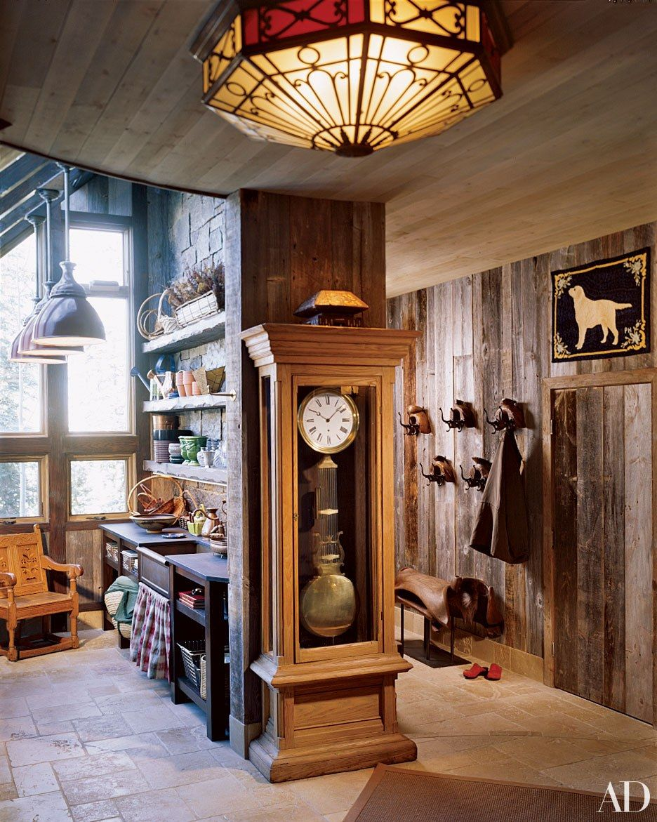 Rough-hewn timber walls line the mudroom of a ski chalet in Telluride, Colorado, renovated by architect John Brons and designer Samuel Botero.