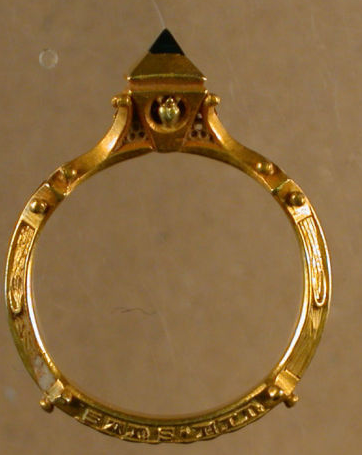 A gold finger ring . Half of a ring cut as a gimmel. The exterior of the hoop is of cable design with engraved flowers extending partially around the hoop on both sides, probably before the 15th century.