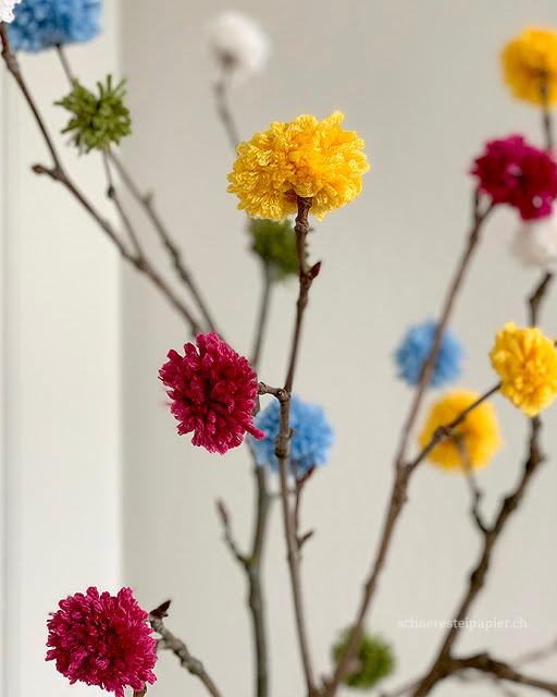 Die Zweige bekommen bunte Blüten – mit Pompoms aus Wolle