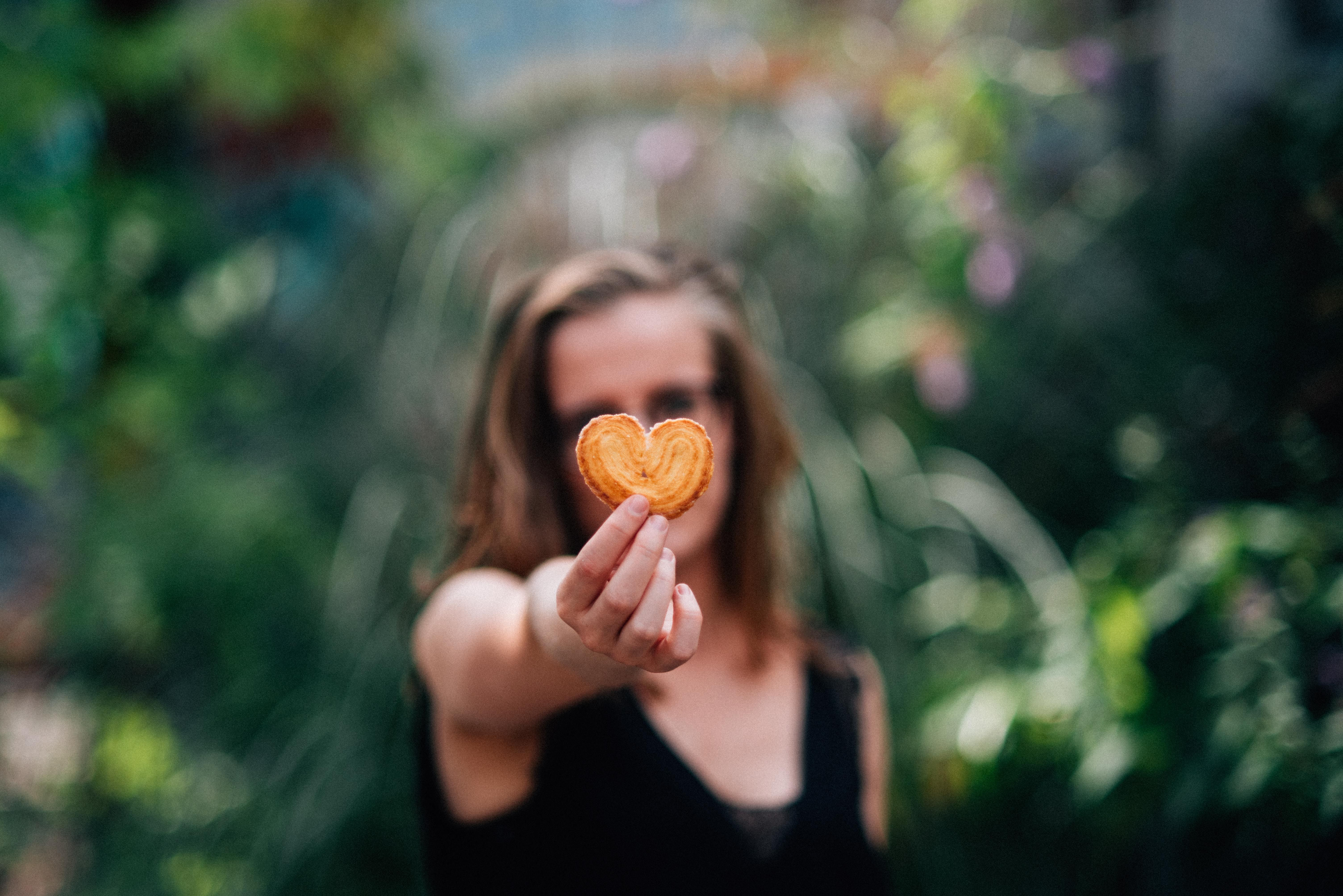 #human  #person  #confectionery #woman #in #black  woman in black top holding heart shaped cookie Amour céréalier
