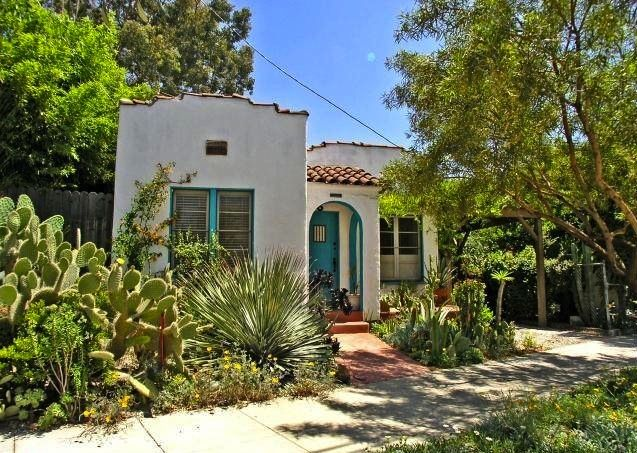 1920s Spanish Style Home With Colorful Windows And Front Door