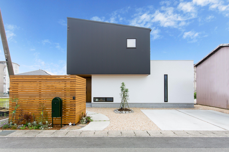 白の塗り壁と黒ガルバのコンビが青空に映える 片流れ屋根の外観