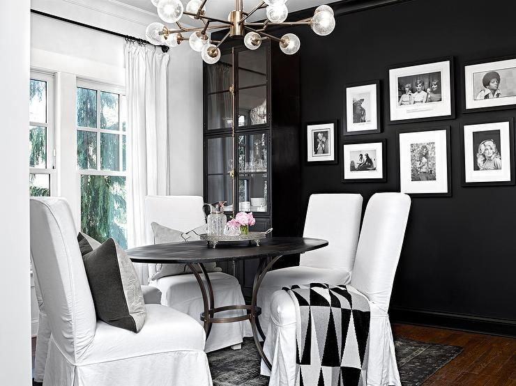 Black And White Dining Room Features A Glass And Brass Modular Chandelier  Illuminating A Round Iron