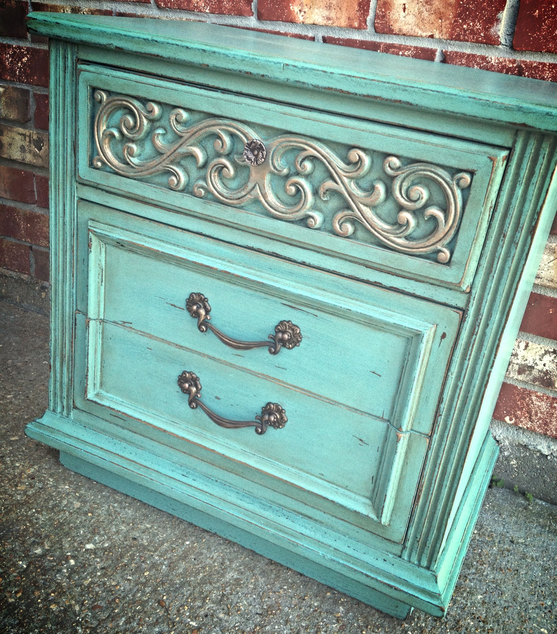 This end table was painted in a custom mix of General Finishes milk paints to create this turquoise color. An antique gold rub buff wax was used on the accent pieces and it was sealed for durability.