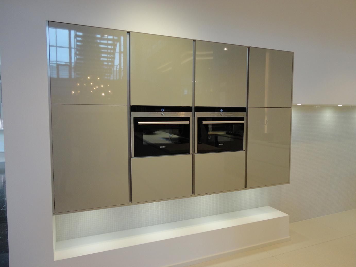 Metallic champagne handleless kitchen doors google search what sets apart a gloss acrylic lacquer and glass kitchen finish from a less costly gloss laminate and vinyl wrap kitchen finish planetlyrics Image collections