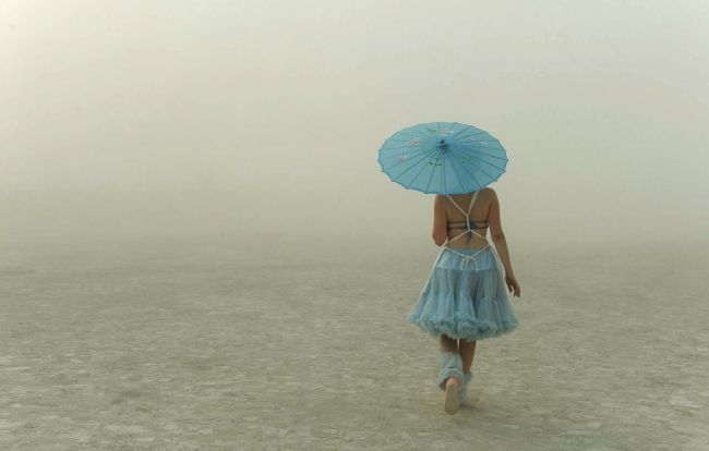 In this Wednesday, Aug. 28, 2013 photo, a young woman walks through the dusty playa at Burning Man in Gerlach, Nev. Once a year, tens of tho...