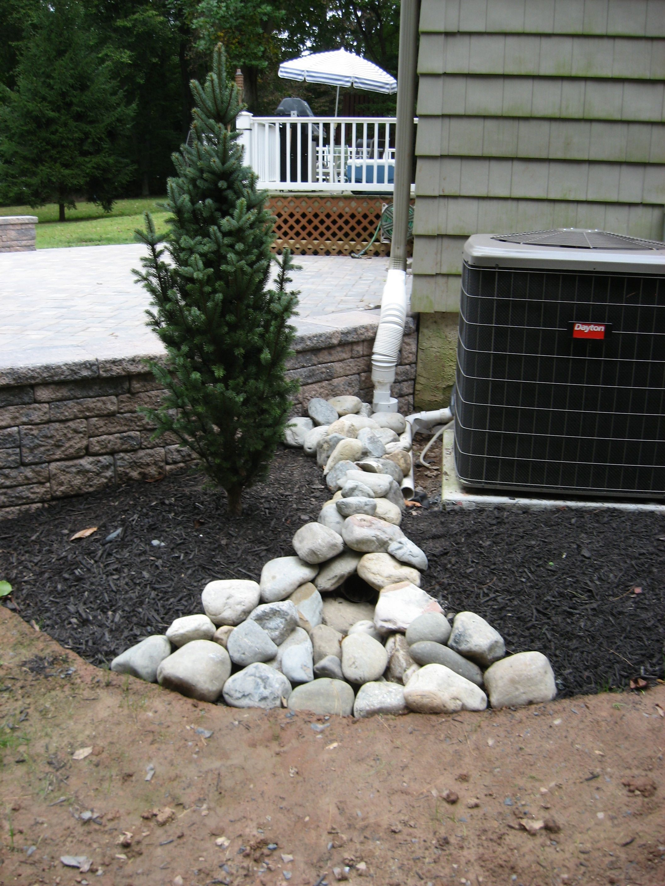 landscaping around patio with river jack rock covering down spout ... - Landscaping Ideas Around Patio
