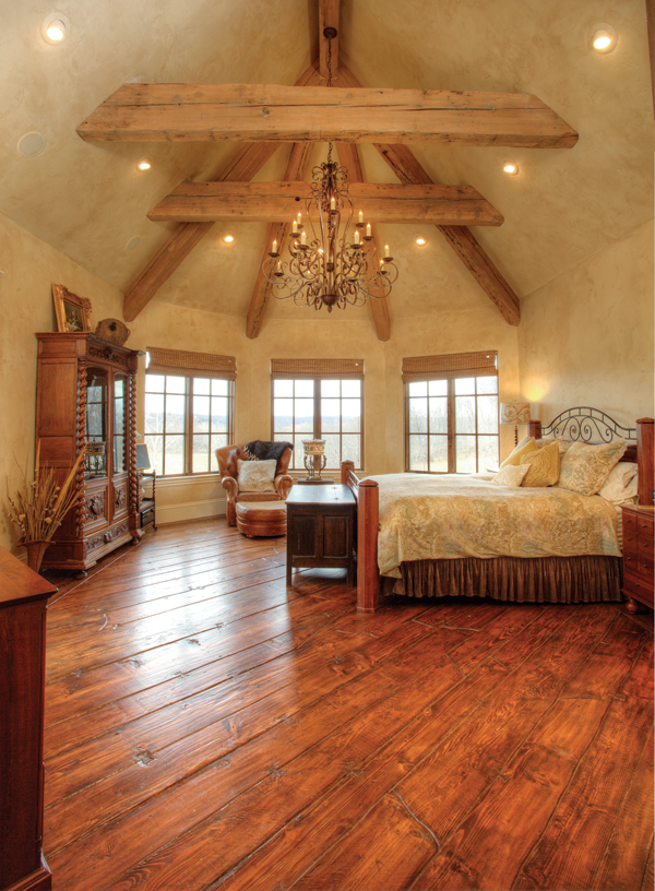 Large reclaimed wood beams make an immediate statement in the master bedroom