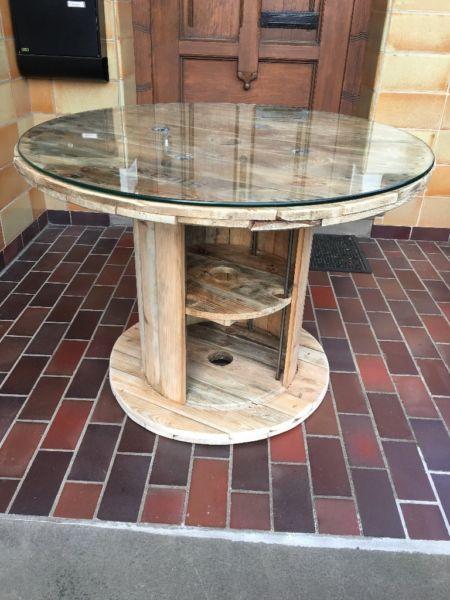 Sie bekommen einen Tisch mit einem Durchmesser von ca. 100cm, welcher aus einer Kabeltrommel gefertigt wurde und ideal als Wohnzimmertisch oder auch individuell für Ihre Zwecke genutzt werden kann. Er sorgt mit seinem rustikalen Design im Vintage-Look für einen echten Hingucker im Wohnzimmer oder in Ihrer Firma und ist garantiert ein echtes Einzelstück.Die Kabeltrommel wurde so bearbeitet, dass sie direkt als Tisch genutzt werden kann. Der Tisch wurde komplett geschmirgelt und die Oberfläche... #cablespooltables