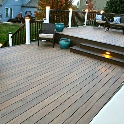 Fully composite timbertech deck with legacy decking in tigerwood and a mocha border railing is timbertech radiancerail express in white and mocha with led
