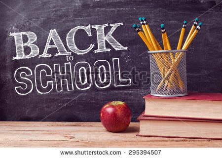 Back to school lettering with books, pencils and apple over chalkboard background