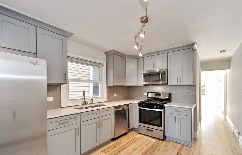 Modern Kitchen With Light Hardwood Floors Grey Cabinets Track